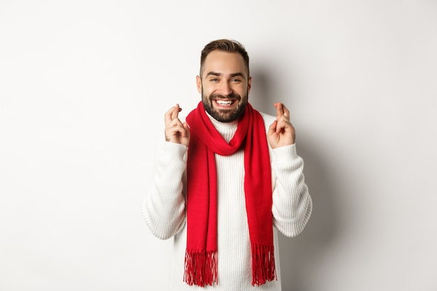 Рождественские каникулы и новогоднее понятие. обнадеживающий человек загадывает желание со скрещенными пальцами, ожидая подарков, стоя на белом фоне.