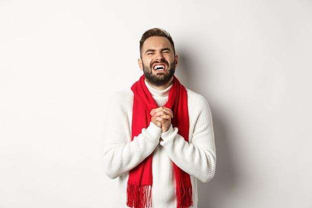 크리스마스 휴일 및 새 해 개념입니다. 도움이 필요한 남자, 애원하고 비참한 표정을 짓고, 무언가에 대해 사과하고, 흰색 배경 위에 서 있습니다.