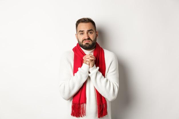 크리스마스 휴일 및 새 해 개념입니다. 도움을 구걸하는 슬픈 남자, 기도하는 손을 잡고 카메라를 보며 괴로워하는 표정, 호의를 구하는, 흰색 배경 위에 서 있는 남자