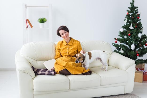 クリスマス、休日、人々の概念-家で本を読んで幸せな若い女性。