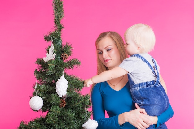 クリスマス、休日、人々の概念-ピンクの背景の上のクリスマスツリーの近くの女性と彼女の子供