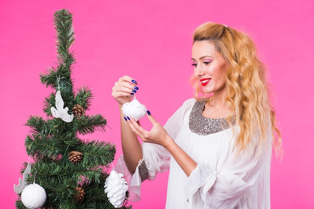 クリスマス、休日、人々のコンセプト-ピンクのスペースにクリスマスツリーを飾る若い幸せなブロンドの女性。