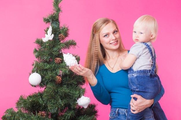 クリスマス、休日、人々の概念-手に娘を持つ若い幸せな女性は、クリスマスツリーの装飾を示しています。