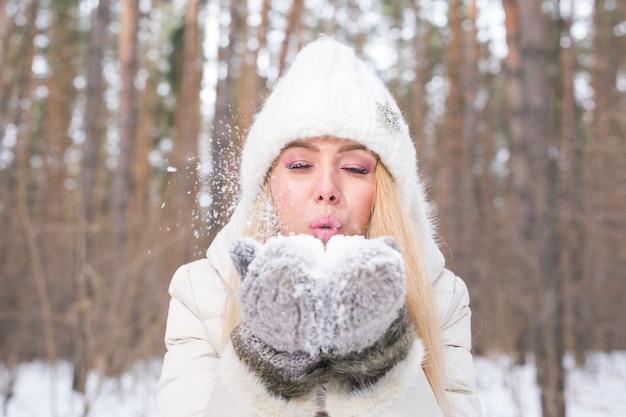 クリスマス、休日、季節のコンセプト-冬の自然の中で雪を吹く若い幸せなブロンドの女性