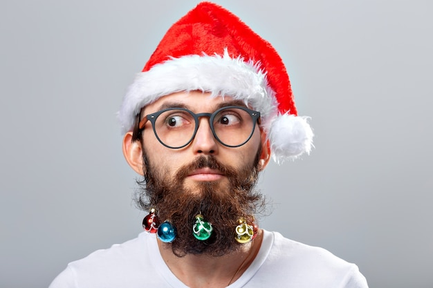 Christmas, holidays, barbershop and style concept - young handsome bearded santa claus man with many small christmas baubles in long beard.