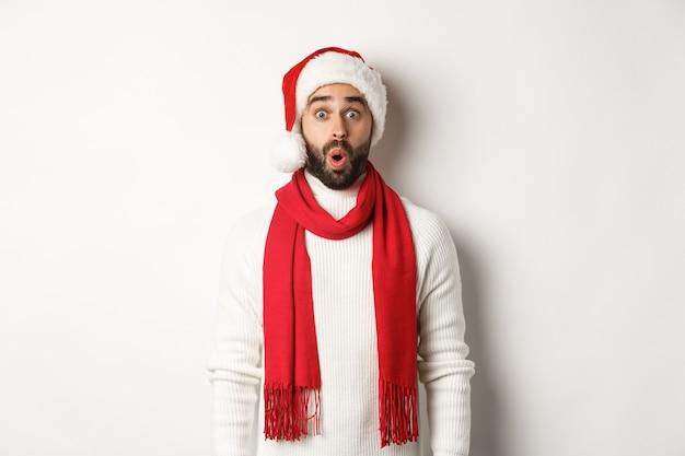 クリスマス休暇。カメラに驚いて見えるひげを生やした男、サンタパーティーハットと赤いスカーフを身に着けて、白い背景に立って
