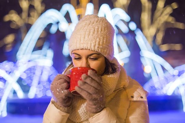 크리스마스 휴일. 겨울에 야외에서 뜨거운 커피 한잔과 함께 따뜻한 옷을 입은 아름다운 웃는 여자. 도시의 밤.