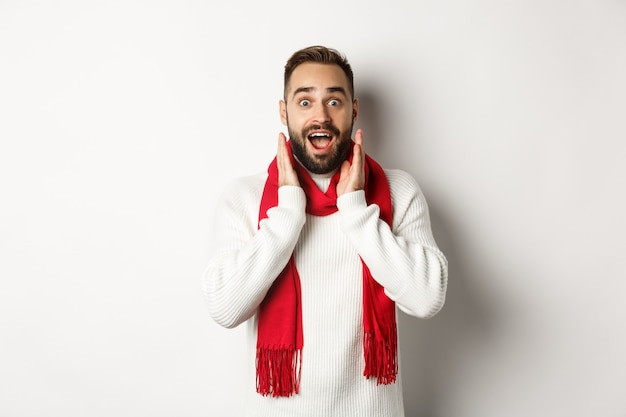 Christmas holidays and celebration concept. bearded guy looking surprised at new year promo offers, gasping amazed, wearing red scarf and sweater, white background