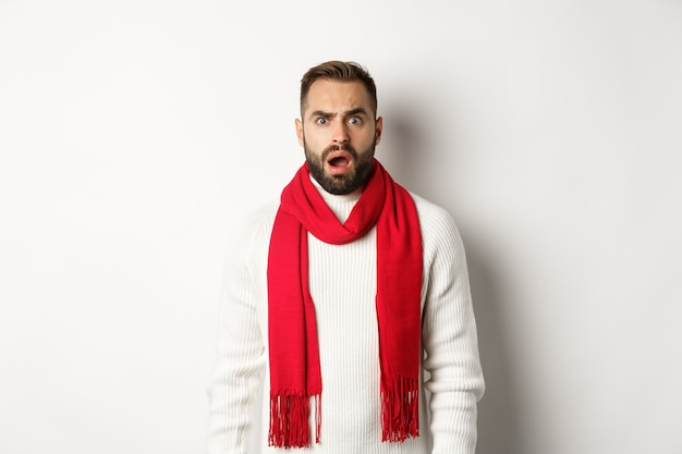 Christmas holidays and celebration concept. confused bearded guy staring at something strange, standing in red scarf and sweater, white background.