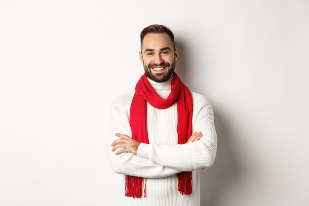 Christmas holidays and celebration concept. handsome bearded man in sweater celebrating new year, wearing red scarf and smiling, standing over white background