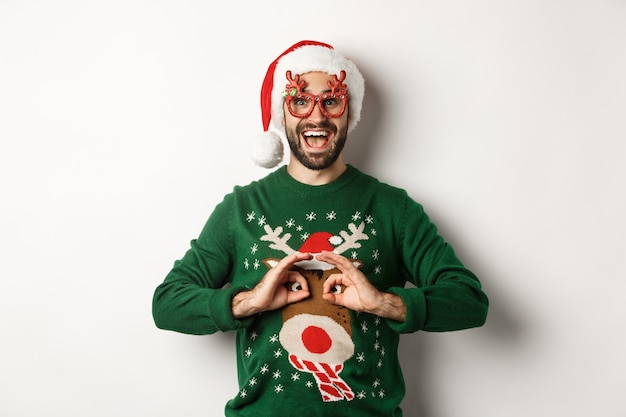 Christmas holidays, celebration concept. happy guy in santa hat and party glasses making fun of funny sweater, standing over white background.