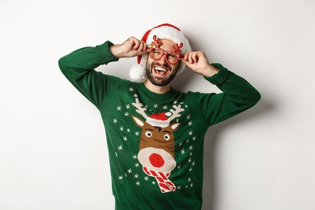 クリスマス休暇、お祝いのコンセプト。サンタの帽子と白い背景に立っている面白いパーティーグラスで幸せな男