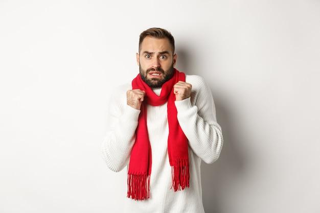 Vacanze di natale e concetto di celebrazione. uomo spaventato che trema di paura e sembra sorpreso, in piedi ansioso con una sciarpa rossa e un maglione bianco