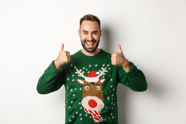 Christmas, holidays and celebration. happy young man enjoying new year party, showing thumbs up in approval, like something good, standing over white background.