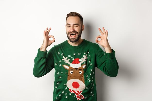 Natale, feste e celebrazioni. felice giovane in maglione verde, strizzando l'occhio e mostrando segni ok, garanzia di qualità, raccomandando qualcosa, sfondo bianco.