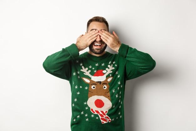 Natale, feste e celebrazioni. felice giovane chiude gli occhi e sorride, in attesa di un regalo a sorpresa, in piedi su sfondo bianco