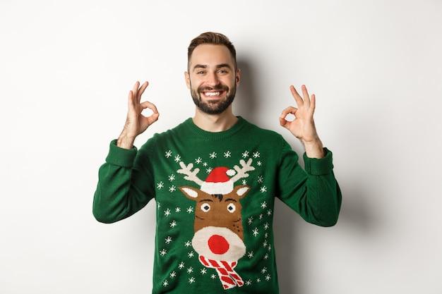 Natale, feste e celebrazioni. uomo sorridente soddisfatto in maglione verde che mostra segni ok e annuisce in segno di approvazione, consigliando il prodotto, in piedi su sfondo bianco.