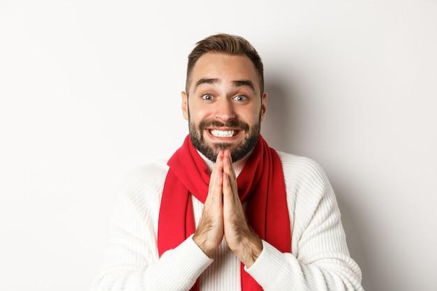 크리스마스 휴일. 수염이 난 남자가 부탁을 하고, 손을 잡고 기도하고 웃고, 귀여운 미소로 구걸하는 클로즈업, 흰색 배경.
