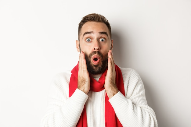 Christmas holidays. close-up of surprised bearded guy saying wow, holding hands near face, standing against white background