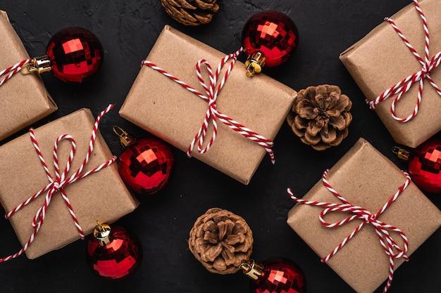Состав рождественских праздников. подарочные коробки, красный орнамент и украшения из сосновых шишек