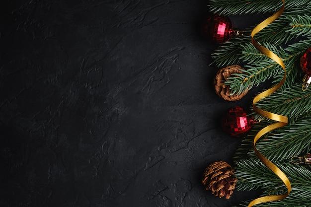 Состав рождественских праздников. золотая лента, красный орнамент и украшения из безделушек, еловые и сосновые шишки. копировать пространство