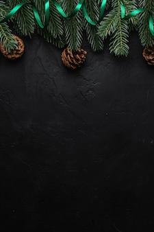 Состав рождественских праздников. зеленая лента, ель и шишки. копировать пространство