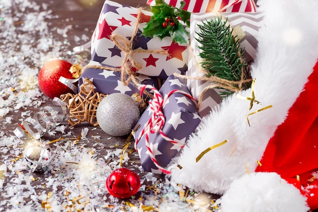 サンタクロースの赤い帽子と木製の背景にギフトボックスとクリスマス休暇の構成