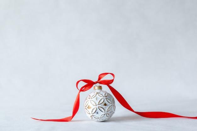 白いボールと赤いリボンのクリスマス休暇組成