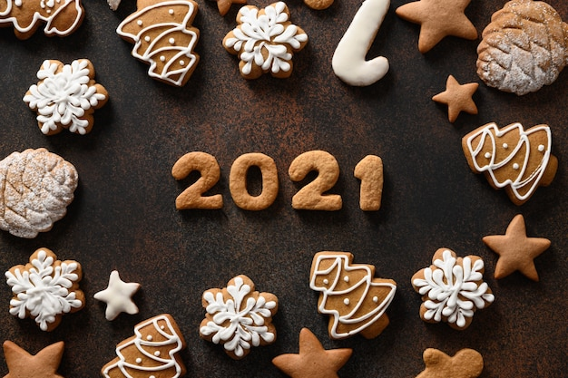 Christmas holidays cookies arranged around date on brown background