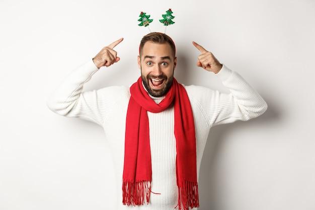 Vacanze di natale. uomo eccitato che celebra le vacanze invernali, indossa un accessorio per la festa di capodanno e una sciarpa rossa, in piedi su sfondo bianco.