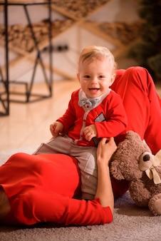 クリスマス、休日、家族と人々の概念-幸せな母と子は家で遊ぶ