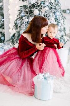 크리스마스 휴일, 가족 개념. 그녀의 작은 달콤한 아름 다운 딸 키스 꽤 젊은 엄마