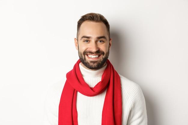 크리스마스 휴일. 빨간 스카프와 스웨터 미소, 흰색 배경에 잘생긴 수염된 남자