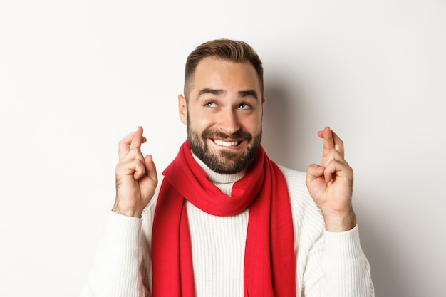 クリスマス休暇。冬の休日に願い事をする幸せな魅力的な男、幸運のために指を交差させ、見上げる、白い背景の上に立って