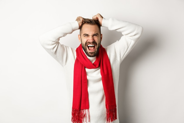 Christmas holidays and new year concept. frustrated and angry man pulling hair off head and screaming distressed, standing mad against white background
