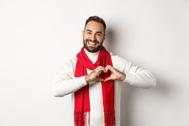 Vacanze di natale e concetto di capodanno. padre felice che mostra il segno del cuore e sorride, ti amo gesto, indossa un maglione invernale e una sciarpa, sfondo bianco