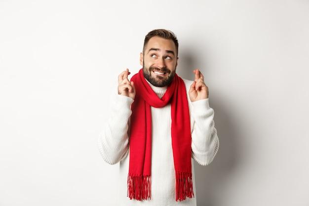 Vacanze di natale e concetto di capodanno. uomo speranzoso che esprime desiderio con le dita incrociate, in attesa di regali, in piedi su sfondo bianco.