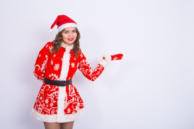 Christmas, holidays and people concept - woman is santa suit pointing with copy space.