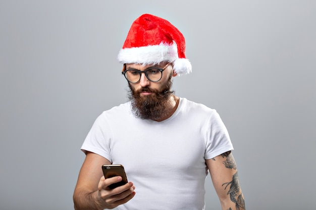 Рождество, праздники, технологии и люди концепции - красивый бородатый мужчина в новогодней шапке, делающий селфи со смартфоном на сером фоне.