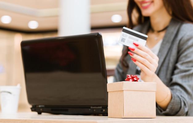 크리스마스, 휴일, 기술 및 쇼핑 개념 - 신용 카드, 선물 상자, 노트북 컴퓨터를 배경으로 웃고 있는 여성. 가로 사진