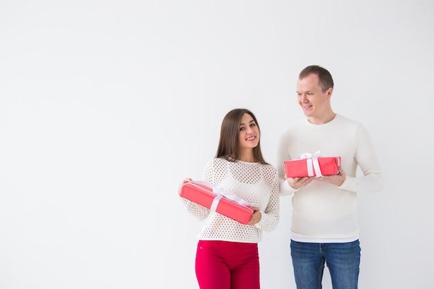 Рождество, праздники, день святого валентина и концепция дня рождения - счастливые мужчина и женщина держат коробки с подарками на белом фоне с копией пространства