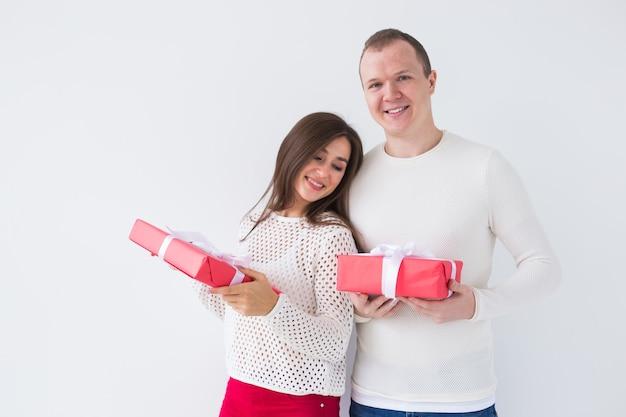 Рождество, праздники, день святого валентина и концепция дня рождения - счастливые мужчина и женщина держат коробки с подарками на белом фоне