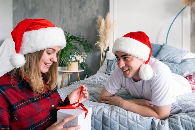 Рождественские каникулы зима и люди концепция счастливая пара с подарочной коробкой дома в шляпах санта-клауса молодой улыбающийся человек, лежащий на кровати, дает своей женщине подарок