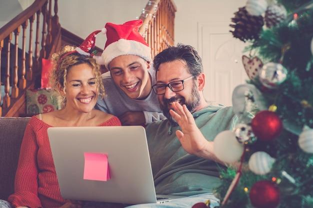 友人や両親にビデオ通話を行うクリスマス休暇冬の家族の家のコンセプト