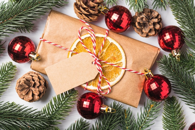Christmas holidays zero waste paper gift wrapping with tag, baubles, dried fruit and fir branches