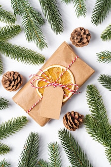 Christmas holidays zero waste paper gift wrapping with tag, dried fruit and fir branches