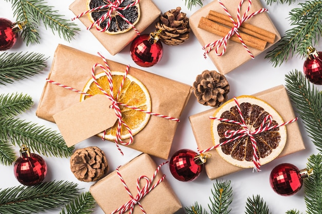 Christmas holidays zero waste paper gifts wrapping with tag, baubles, dried fruit and fir branches