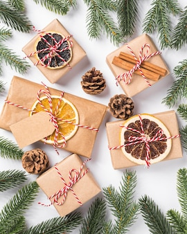 Christmas holidays zero waste paper gifts wrapping with tag, dried fruit and fir branches