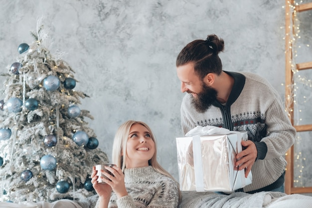 Christmas home celebration. guy surprised his girlfriend with gift. lady sitting on couch with hot drink, smiling.