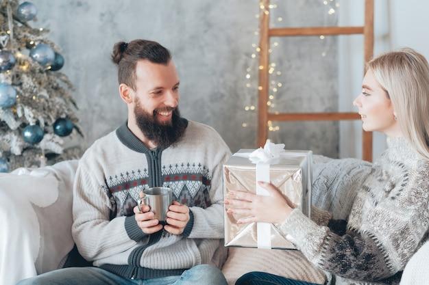 크리스마스 홈 축하. 그녀의 남자 친구를위한 선물 상자를 들고 레이디